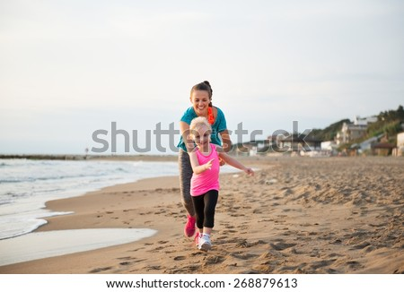 Healthy mother and baby girl running on beach - stock photo