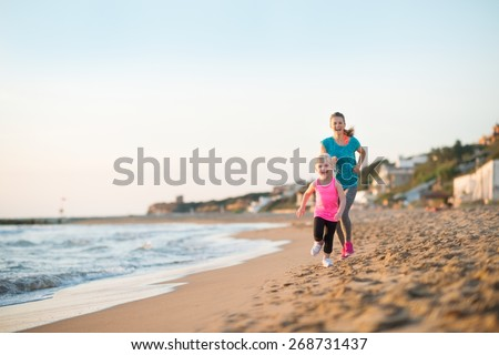 Healthy mother and baby girl running on beach in the evening - stock photo