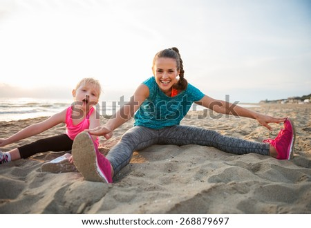 Healthy mother and baby girl stretching on beach in the evening - stock photo