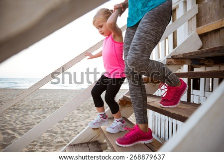 Healthy mother and baby girl walking down the stairs - stock photo