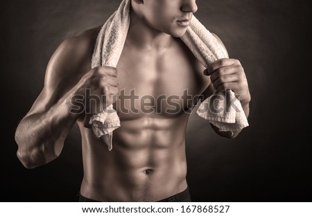 Healthy muscular young man after a workout on dark background - stock photo