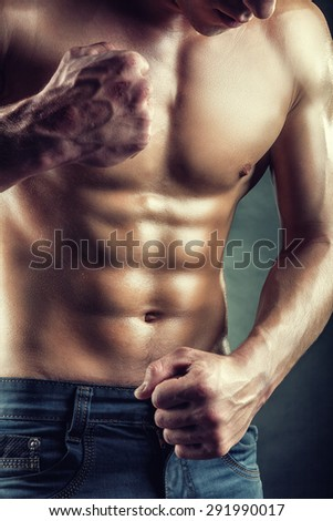 Healthy muscular young man on a dark background - stock photo
