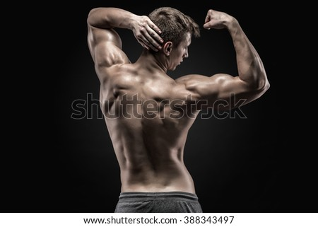 Healthy muscular young man showing back and biceps muscles - stock photo