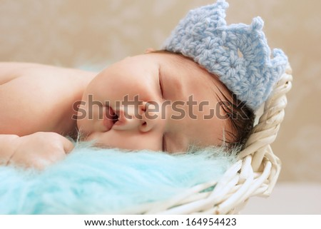 Healthy newborn baby in close up wearing blue knitted prince's crown - stock photo