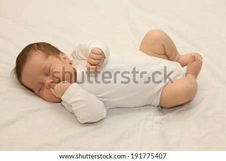 Healthy newborn baby sleeping on white sheet - stock photo