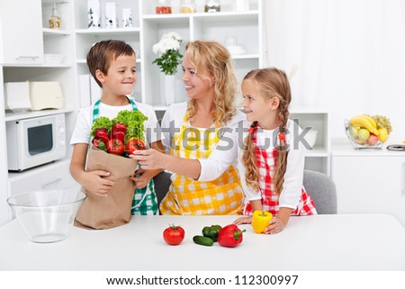 Healthy nutrition concept with people in the kitchen unpacking the vegetables from grocery bag - stock photo