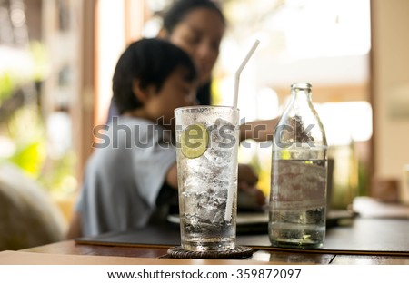 Healthy nutrition of drinking water with lemon and people in blur background - stock photo