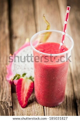 Healthy nutritious tropical smoothie with strawberries and dragon fruit blended with yoghurt or ice cream on a rustic wooden table top - stock photo