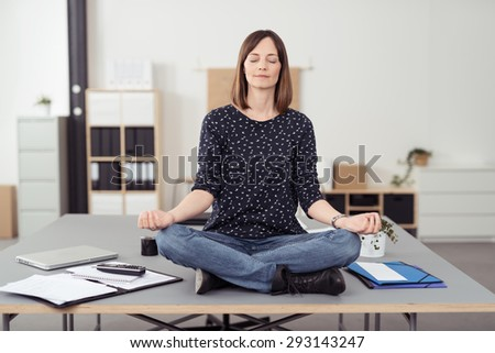 Healthy Office Woman Sitting on the Table at the Boardroom While Doing Yoga Exercise In Front of the Camera. - stock photo