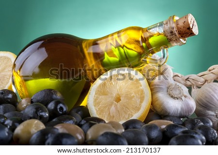 Healthy olive oil with black and green olives, lemon and garlic - stock photo