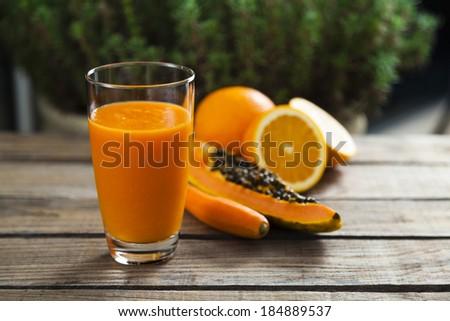 Healthy orange, papaya and carrot smoothie - stock photo