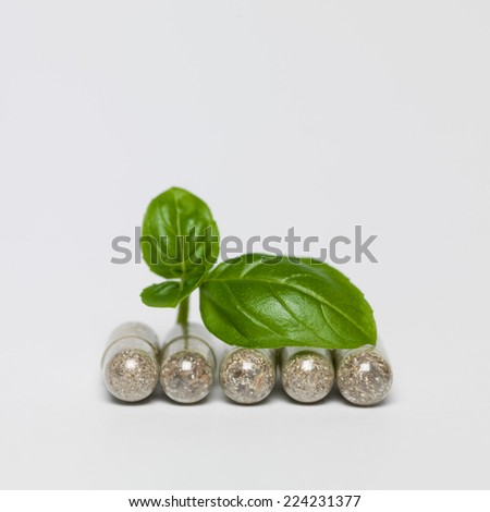 healthy organic capsules in a row with green leaf on white background - stock photo