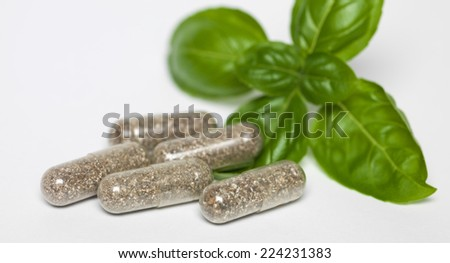 healthy organic capsules with green basil leaf isolated on white background - stock photo