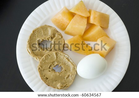 Healthy Organic High Protein Breakfast, Whole Wheat Bagel with Peanut Butter, Hard Boiled Egg and Cantaloupe isolated black - stock photo