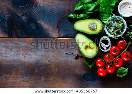 Healthy organic ingredients for salad making: avocado, spinach, tomatoes, sprouts, basil, olive oil on rustic background, top view. Flat lay with place for text. Vegan and healthy food concept - stock photo