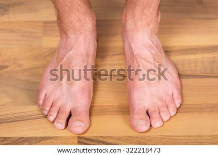 Healthy pair of male toes without fungus or other skin problems on the floor. - stock photo