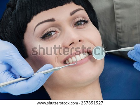 Healthy patient. Dentist makes the process of treatment of a beautiful young girl. - stock photo