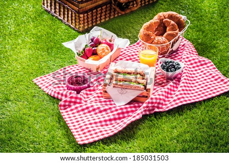 Healthy picnic for a summer vacation with freshly baked croissants, fresh fruit and fruit salad, sandwiches and a glass of refreshing orange juice laid out on a red and white checked cloth and hamper - stock photo