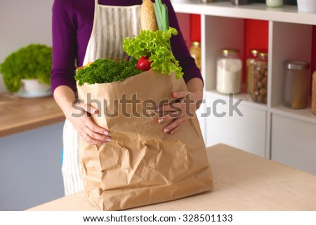 Healthy positive happy woman holding a paper shopping bag full of fruit and vegetables. - stock photo