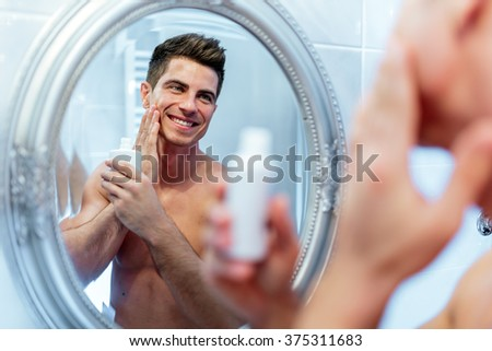 Healthy positive male treating skin with lotion after shaving - stock photo