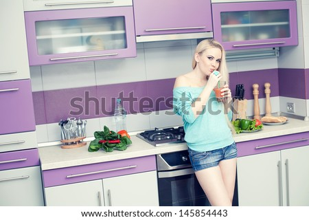 Healthy pregnancy concept. Portrait of a lovely young pregnant woman drinking fresh orange juice through sipper in her modern hi-tech kitchen. Trendy clothing on girl. Copy-space. Indoor shot - stock photo