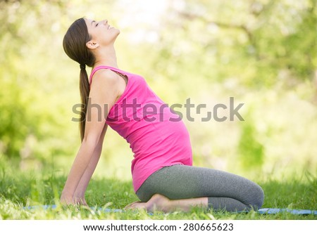 Healthy pregnant woman doing yoga in nature outdoors. - stock photo