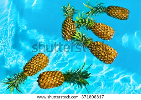Healthy Raw Organic Food. Fresh Ripe Pineapples Floating In Pure Water In Swimming Pool. Juicy Fruit. Vegetarian, Vegan Nutrition, Lifestyle. Eating Vitamins. Diet, Beauty, Health, Hydration Concept - stock photo