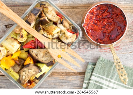 Healthy roast or grilled Turkish style vegetables served with zucchini, eggplant and sweet peppers served with a bowl of piquant hot spicy pepper paste, overhead view - stock photo
