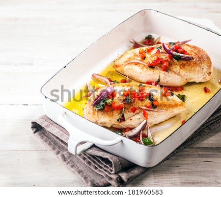 Healthy roasted or barbecued chicken breasts with a golden texture topped with a savory garnish of fresh diced herbs, red pepper and onion served in a roasting pan on a light wood table, square format - stock photo