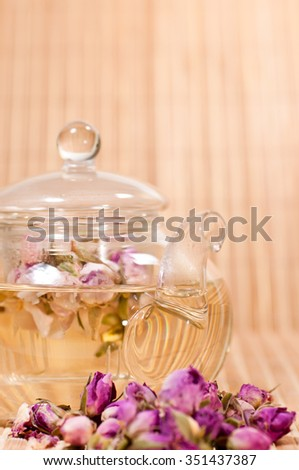 Healthy rose tea brew in a glass teapot on bamboo mat background - stock photo