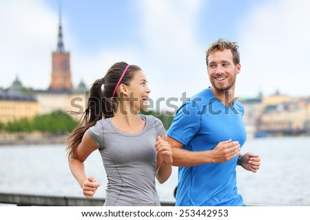 Healthy runners running in Stockholm city cityscape background. Riddarholmskyrkan church in the background, Sweden, Europe. Healthy multiracial young adults, asian woman, caucasian man. - stock photo