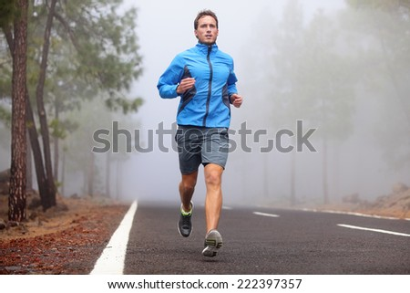 Healthy running runner man workout on mountain road. Jogging male fitness model working out training for marathon on forest road in amazing nature landscape. - stock photo