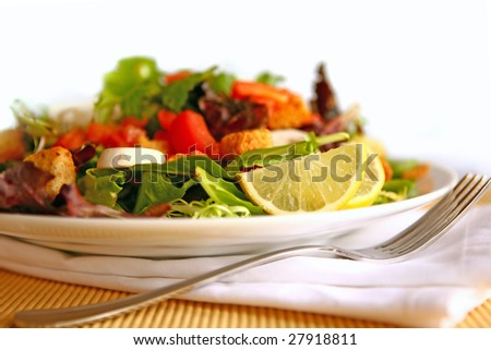 Healthy Salad on a Plate With Focus on Lemon - stock photo
