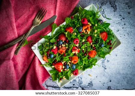 Healthy salad with arugula,spinach,smoked salmon and berries - stock photo