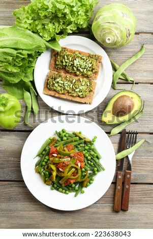 Healthy salad with peas and asparagus served on wooden table, close-up - stock photo