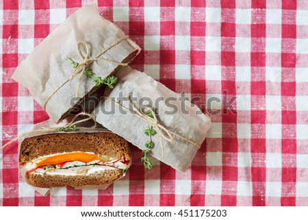 Healthy sandwich made of a fresh rye roll with tasty ingredients of ham, tomato, lettuce and arugula top view, copy space - stock photo