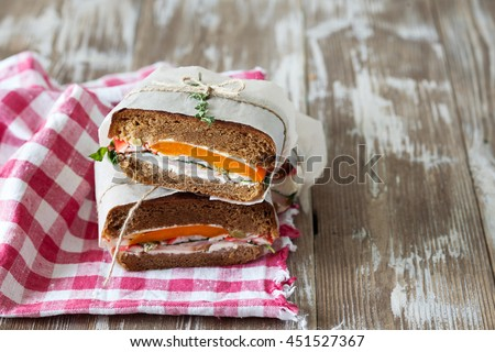 Healthy sandwich made of a fresh rye roll with tasty ingredients of ham, tomato, lettuce and arugula, presented on old wooden board, copy space - stock photo