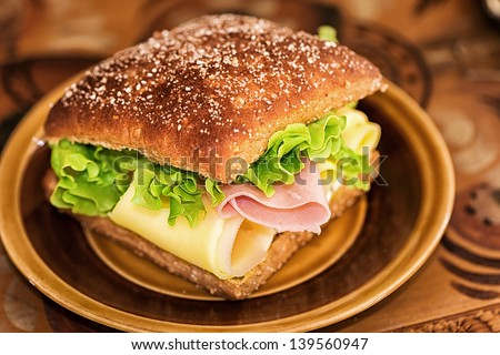Healthy sandwich with lettuce, cheese and ham on a brown plate and background - stock photo