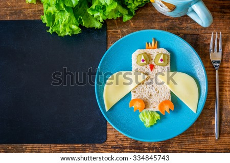 Healthy school lunch for kids. Funny owl sandwich and salad on wooden table plus empty black chalkboard for text. Copy space, table top view - stock photo