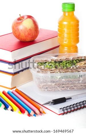 Healthy school lunch with school supplies on white isolated background - stock photo