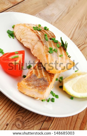 healthy sea food : roasted pink salmon fillet on white dish over wooden table - stock photo