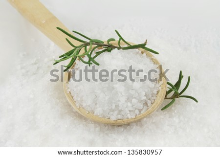 Healthy sea salt on wooden spoon closeup, and rosemary - stock photo