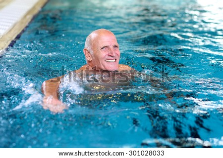 Healthy senior man swimming in the pool. Happy pensioner enjoying sportive lifestyle. Active retirement concept. - stock photo