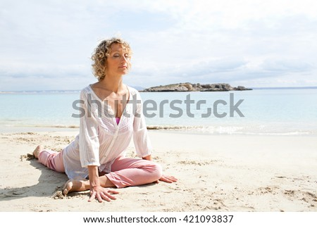 Healthy senior woman stretching in yoga position, meditating on the shore of a sea in a coastal beach destination with eyes closed, sunny outdoors. Sporty travel lifestyle, spacious nature exterior. - stock photo