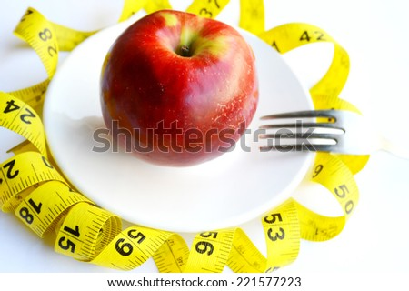 Healthy slimming, red apple,fruits for weight loss, a measuring tape, diet, weight loss - stock photo