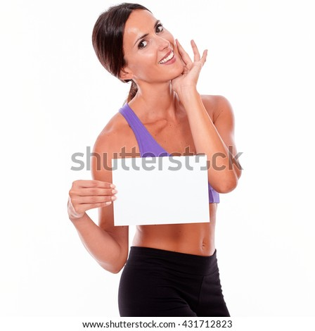 Healthy smiling brunette woman holding blank signboard and a hand on her chin looking at camera while wearing violet and black gymnastic clothing, isolated - stock photo