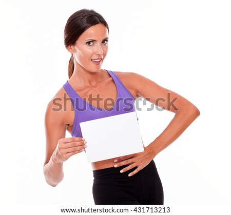 Healthy smiling brunette woman holding blank signboard and a hand on her waist looking at camera while wearing violet and black gymnastic clothing, isolated - stock photo