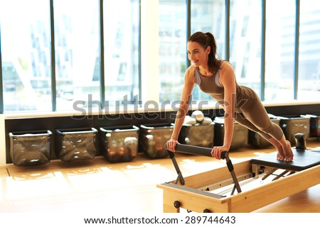 Healthy Smiling Brunette Woman Wearing Leotard and Practicing Pilates in Exercise Studio - stock photo