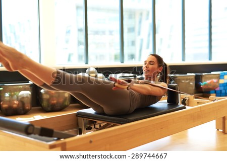 Healthy Smiling Brunette Woman Wearing Leotard Practicing Pilates in Bright Exercise Studio - stock photo