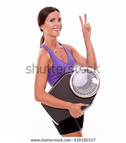 Healthy smiling brunette woman with a scale, gesturing a peace sign while wearing her hair tied back and violet and black gymnastic clothing, isolated - stock photo